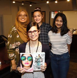 "Teens from Tucson High School pose with Guadalupe Garcia McCall, her book ""Shame the Stars"" and their gift of Tucson pan dulce."